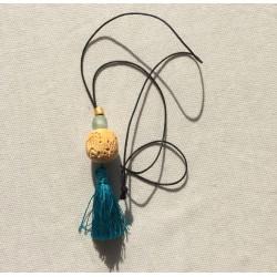 Collar largo combinación de pompom turquesa con pieza africana labrada de marfil, cristal color hielo y pieza dorada